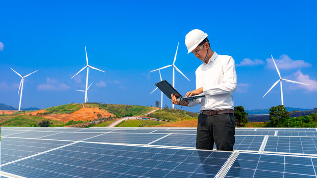 Electrical engineers are using tablets to monitor the operation of the solar cells. Renewable energy concepts.