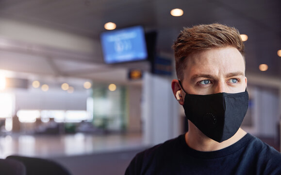 Male waiting in airport wearing protective face mask