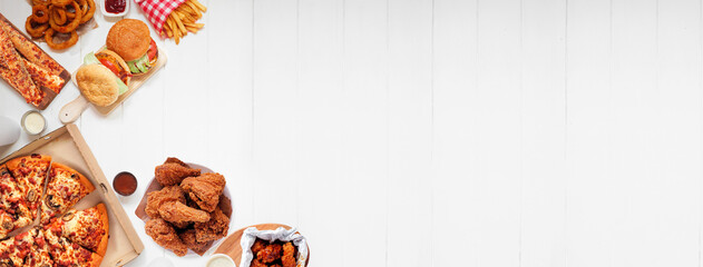 Selection of take out and fast foods. Corner border banner. Pizza, hamburgers, fried chicken and sides.  Top down view on a white wood background with copy space.