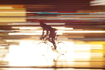 Fotomurales - Silhouette Man Riding Bicycle With Light Trails On Road