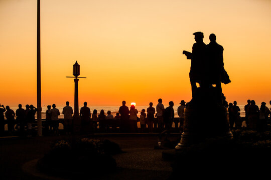Crowd of people watching sunset  at Seaside, Oregon at the turnaround.  Historically the Turnaround is where Lewis & Clark ended their journey.