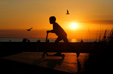 A boy plays with a scooter during the sunset at a skate park on the sea wall of Calais