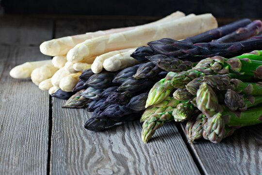 Raw white, purple, green asparagus on a dark wooden background. Raw food concept, place for copy space.