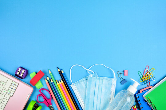 School supplies and coronavirus prevention items. Bottom border on a blue paper background. Back to school during pandemic concept.