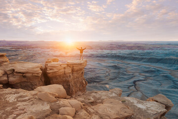 Man stands triumphant with his hands outstretched in victory while standing on a cliff looking into the sunset and sunrise
