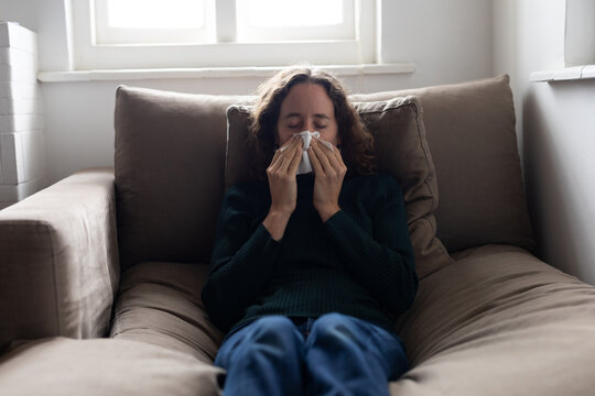 Woman blowing her nose on the couch at home
