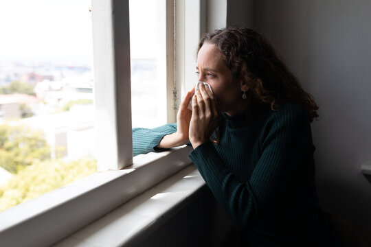 Woman blowing her nose near the window at home