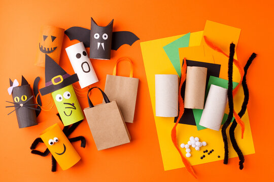 Child creates decorations for Halloween party from toilet roll. Easy eco-friendly DIY master class, craft for kids. Materials for creativity, recycle reuse concept of holiday art activities