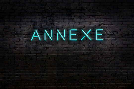 Night view of neon sign on brick wall with inscription annexe