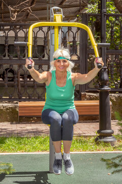 Slender elderly woman with gray hair conducts individual fitness classes on a simulator in a city park