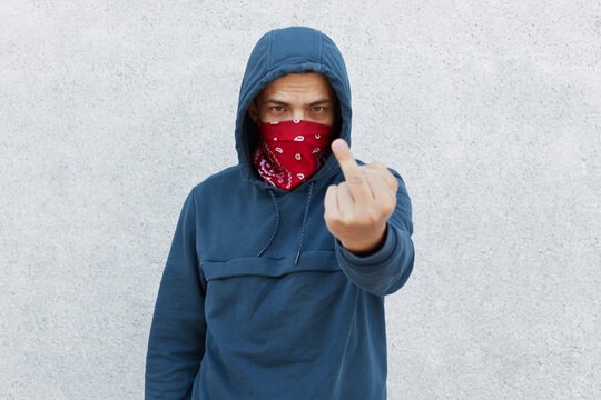 Close up photo of young guy in bandana mask calls for stopping police brutality, showing fuck symbol, fight for equal rights and against racism isolated over white background.