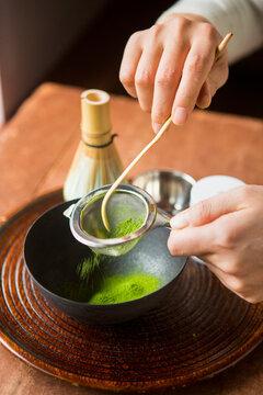 Woman sifting matcha tea traditional Japanese style.
