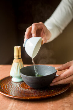 Woman pouring water in a bowl to make matcha tea traditional Japanese style.