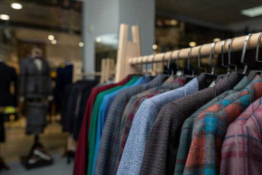 expensive men's clothing store. a row of jackets on hangers. shoping sale background theme. clothes on hanger in shop