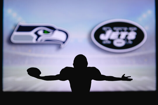 Seattle Seahawks vs. New York Jets. NFL Game. American Football League match. Silhouette of professional player celebrate touch down. Screen in background.