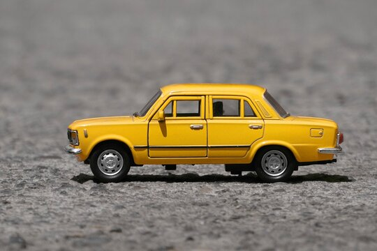 yellow toy car on the road