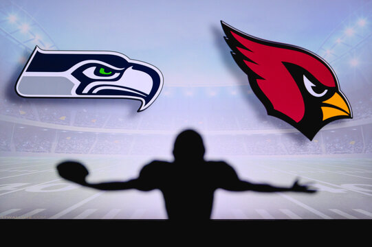 Seattle Seahawks vs. Arizona Cardinals . NFL Game. American Football League match. Silhouette of professional player celebrate touch down. Screen in background.