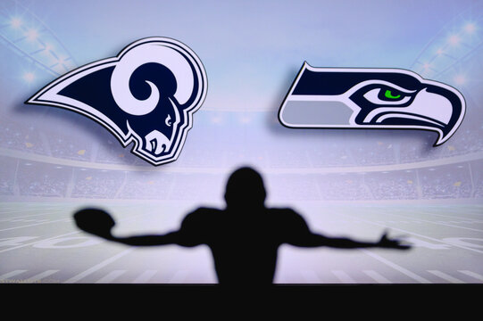 Los Angeles Rams vs. Seattle Seahawks. NFL Game. American Football League match. Silhouette of professional player celebrate touch down. Screen in background.