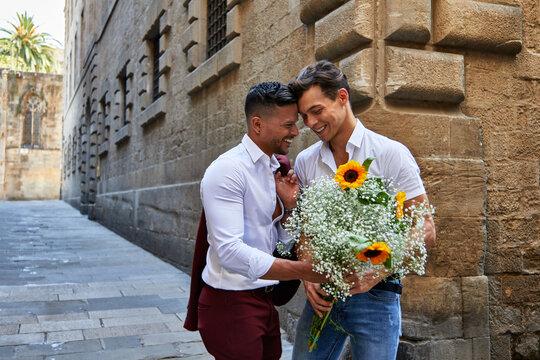 Pareja gay en Barcelona con flores mostrando amor y ternura