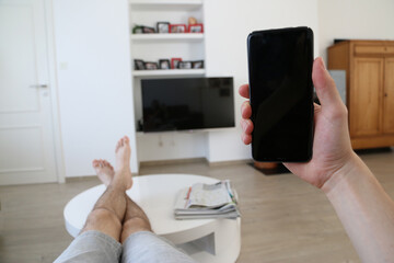 Hand holding a very modern mobile phone with a black touch screen. The man is laying with his  bare legs and feet on the little coffee table. In the interior, a turned off TV is hanging from the wall.