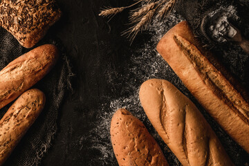 Variety of delicious breads and buns on dark slate background with wheat spikiletes, sackcloth. Pastries and bread in a bakery. Food concept, top view