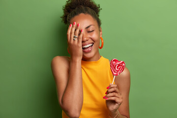 Photo sur Toile Les Textures Joyous black girl makes face palm, smiles broadly, closes eyes, poses with heart lollipop on stick, has fun indoor, holds yummy candy, wears yellow t shirt, stands against green vivid background