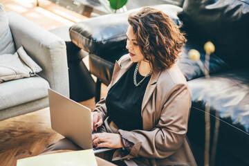 Fotobehang Berlijn Caucasian brunette woman sitting near the sofa in living room and using laptop for freelance job.