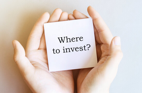 white paper with text Where to invest in male hands on a white background