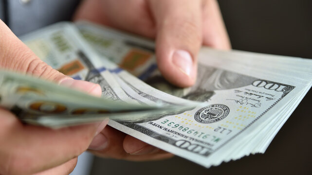 Close up of businessman counts money in hands.