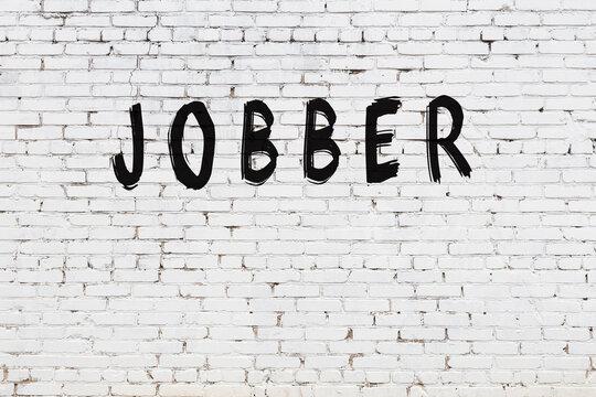 Inscription jobber painted on white brick wall