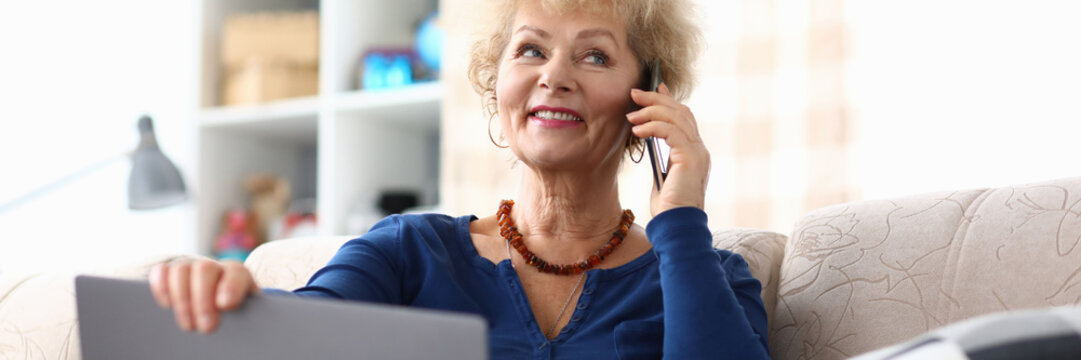 Portrait of happy smiling woman talking to somebody on mobile phone. Elderly female order delivery via laptop. Goes with the times. Modern technology concept