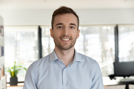 Profile picture of happy young Caucasian male employee worker look at camera posing in office workplace, headshot portrait of smiling businessman boss show confidence and success, leadership concept