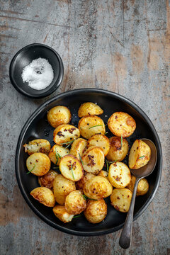 Roasted Potatoes with Mustard and Rosemary Top View on Timber