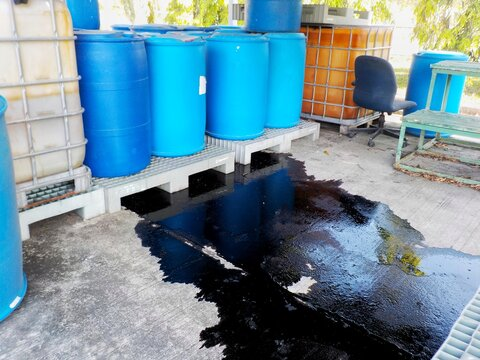 Black liquid chemicals leaking from the tank into the floor.