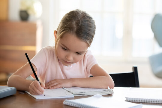 Busy little girl writing or drawing with pen in notebook close up, pretty focused child schoolgirl preparing school homework, assignments, sitting at work desk at home, homeschooling concept