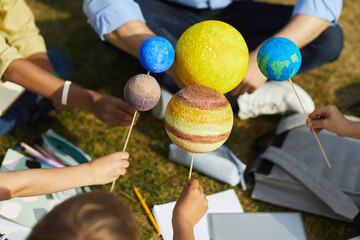 Close up of group of children holding model planets while enjoying outdoor astronomy class in sunlight, copy space