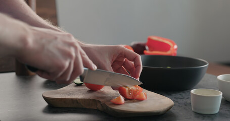 man chop tomatoes on olive wood board