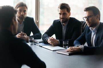 Focused young male group of employers in formal suits sitting at table with vacancy candidate, involved in job interview in office. Attentive confident hr managers listening to seeker at meeting.