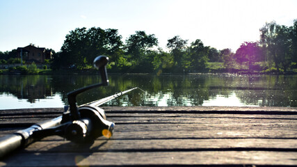 Fishing. Rod, spinning reel on the lake. Fishing for peace fish. Wild nature. River in sun rays....