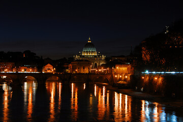 Night in Rome. View of the city along River Tiber with the iconic St Peter illuminated in a romantic atmosphere