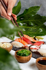 Close up of hand taking suchi with chopsticks from a plate