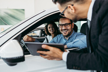 Middle age couple choosing and buying car at car showroom. Car salesman helps them to make right...