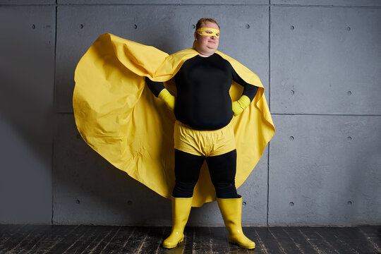 handsome brave strong man has a mad desire, a dream to shield the world from dirt and evil. fat superhero in yellow costume posing isolated over gray background