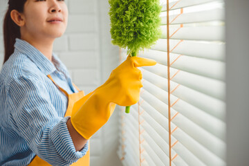 Young asian woman cleaning house wiping dust using Feather broom and duster while cleaning on window House keeping concept