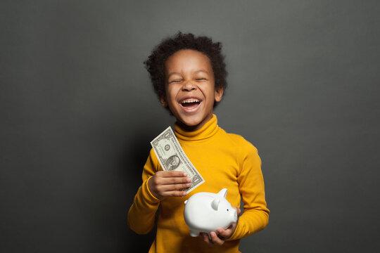 Smart happy black child boy putting in piggy bank one dollars banknote