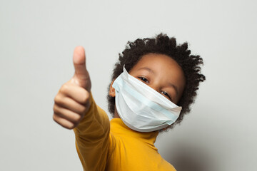 Wall Murals Akt Happy African American black kid in medical protective face mask showing thumb up on white