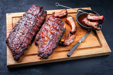 Barbecue pork spare loin ribs St Louis cut with hot honey chili marinade burnt as closeup on a wooden cutting board