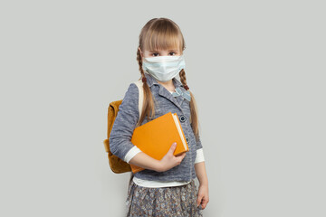 Cute little girl wearing medical protective face mask on white background