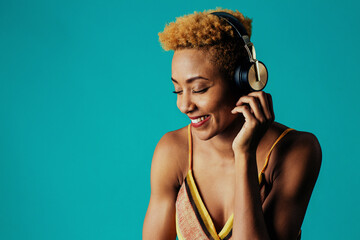 Profile portrait of a smiling young  woman with headphones listening to music with eyes closed
