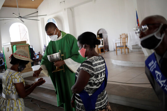 A Catholic faithful, wearing a face mask, takes communion during a mass on the first day of the reopening of temples and worship places, amid the coronavirus disease (COVID-19) outbreak, at the Cathedral of Port-au-Prince